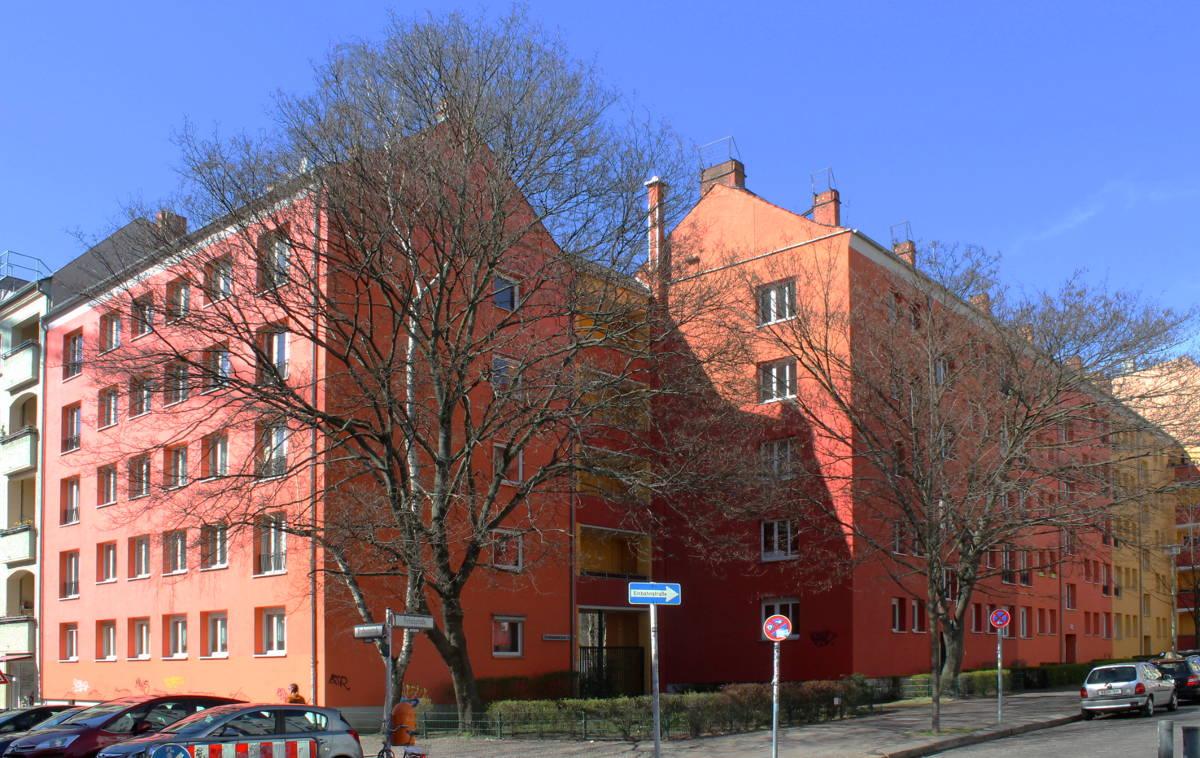 Hausecke mit Straßenbäumen und Straßenschild und Verkehrsschildern