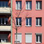 Rötliche Fassade mit Balkonen und Fenstern. Foto: Anna Jauch