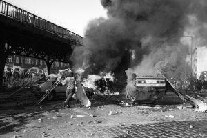 Schwarz-weiß-Foto: zwei brennende Autos, Rauchschwaden, Pflastersteine