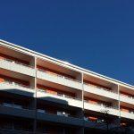 Blauer Himmel über Plattenbau mit grauen Balkonbrüstungen