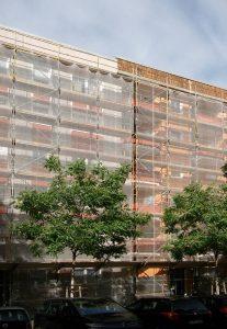 Fassade an der Marchlewskistraße mit neuen Farben hinter Netzvorhang