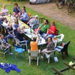 Bewohner sitzen um großen Tisch auf einer Wiese. Foto: Rico Neuber