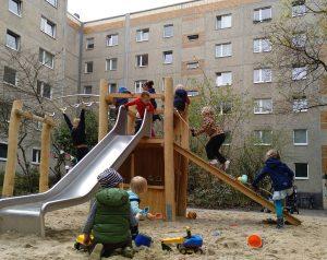 Kinder spielen im Sand und Klettern auf Holzspielgerät mit Rutsche.