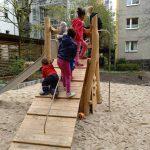 Kinder auf der Kletterrampe des Holzspielgeräts