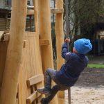Kind erklimmt das Holz-Spielgerät an der Kletterstange