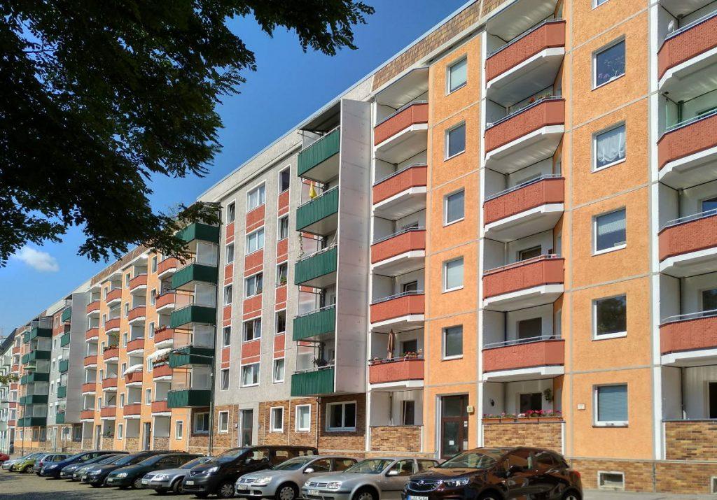 Sonnenbeschienene Plattenbaufassade in orange, rot und weiß; davor parkenden Autos