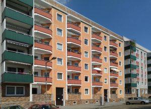 lattenbaufassade in orange, rot und weiß, vorgestellte Balkone mit dunkelgrüner Brüstung