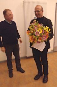 Zwei Herren, einer mit Blumenstrauß und Mikrofon in der Hand
