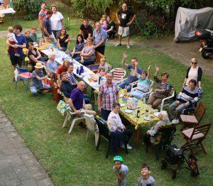 Lange Festtafel auf der Wiese mit zahlreichen Personen