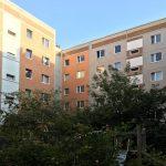 Begrünter Innenhof, Plattenbaufassade mit orangefarbenem und grauem Anstrich