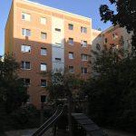 Begrünter Innenhof mit Spielplatz, Plattenbaufassade mit orangefarbenem und grauem Anstrich