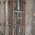 Senkrecht verlaufende Leitungen und Holzlatten vor Betonwand
