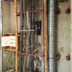 Wandöffnung mit Rohren und Kabeln sowie Sicherungskasten vor Betonwand.