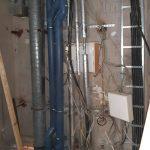 Wasser- und Elektrikleitungen vor Betonwand
