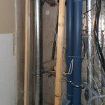 Verschiedene neue Rohr- und Elektroleitungen, Holzlatten im gegöffneten Schacht