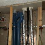Verschiedene Rohr- und Elektroleitungen, Holzlatten, die auf eine erneuerte Zwischendecke treffen.
