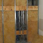 Schachtwand halb geschlossen mit Holzplatten, durch Öffnungen sind glänzende Rohre sichtbar