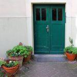 Eingangstür mit Pflanzkübeln davor, Foto: Anna Jauch