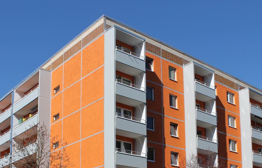 Plattenbau-Eckgebäude in Orange und Grau unter blauem Himmel