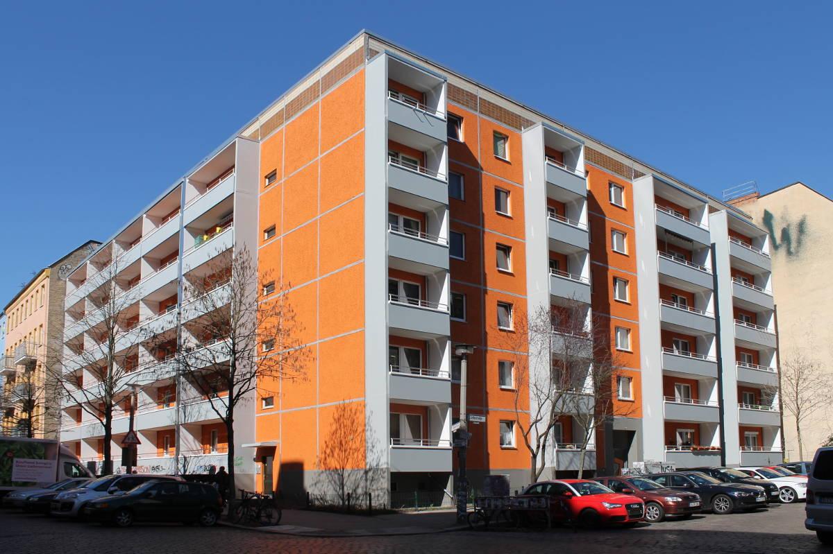 Plattenbau-Eckgebäude in Orange und Grau.