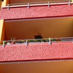 Balkone in Rot und Gelb mit Blumenkästen