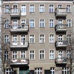 Altbaufassade mit grauem Kratzputz und Balkonen