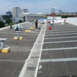 Arbeiter, Material und Geräte auf Flachdach, im Hintergrund Hochhaus-Skyline