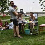 Festteilnehmer*innen an einem kleinen Tisch und auf der Wiese sitzend; Foto: Markus Laux