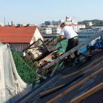 Dachdecker am Aufzug, Blick über Dächer im Hintergrund
