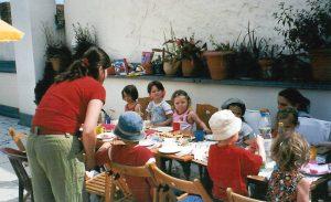 Kinder an langer Tafel
