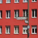 """Rote Fassaden mit Fenstern, Straßenschild """"Marchlewskistraße"""" im Vordergrund"""