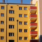 Fassade in Gelb mit roten Balkonen