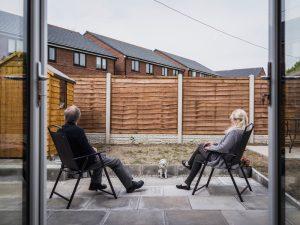 Älteres Paar auf Terrasse schaut auf Holzzaun