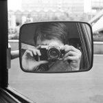Selbstportrait in Auto-Außenspiegel, schwarz-weiß