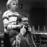 Frau klebt Mann künstlichen Schnurrbart an, schwarz-weiß