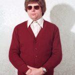 Mann mit Sonnenbrille, in roter Strickjacke
