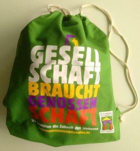 "Grüner Stoffbeutel mit bunter Beschriftung ""Gesellschaft braucht Genossenschaft"""