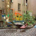 Bänke, Tisch, Pflanzen, bemalte Wände, gepflasterter Weg